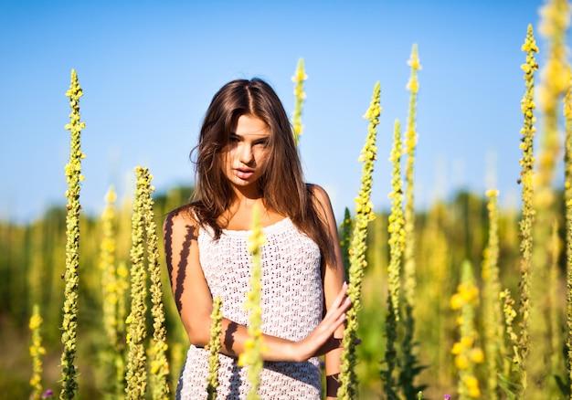 Giovane donna sexy in mini abito bianco in piedi con gli occhi chiusi e godendo il sole