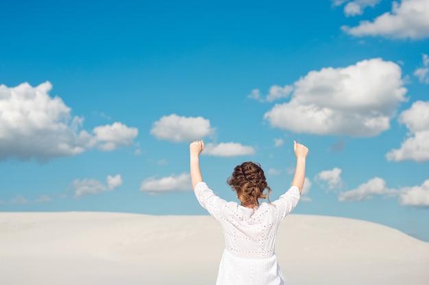 Giovane donna sicura che alza il suo pugno nel cielo. sentirsi motivati