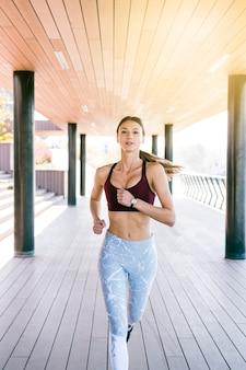 Giovane donna sicura di forma fisica che corre di mattina