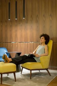 Giovane donna sittinh su una sedia gialla e leggendo un libro
