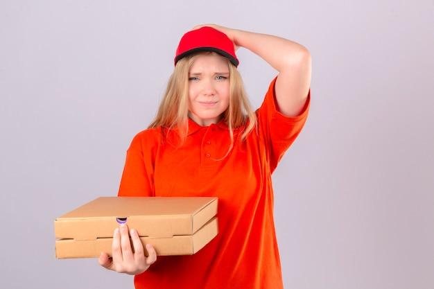Giovane donna smemorata di consegna in maglietta polo arancione e berretto rosso che tiene scatole per pizza tenendo la mano sulla testa mentre si rende conto che si è dimenticata di fare qualcosa di importante sul retro bianco isolato