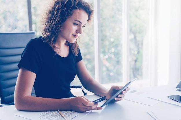 Giovane donna soddisfatta della carta di credito vincolante per l'account online tramite tavoletta digitale per acquisti sul negozio online e altri pagamenti.
