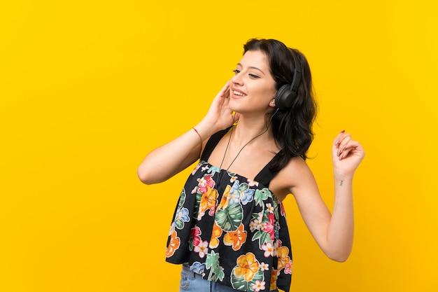 Giovane donna sopra fondo giallo isolato che ascolta la musica con le cuffie