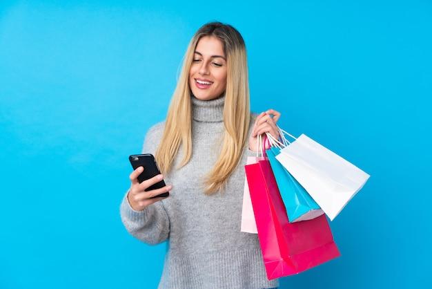 Giovane donna sopra i sacchetti della spesa isolati della tenuta della parete blu e scrivere un messaggio con il suo telefono cellulare ad un amico