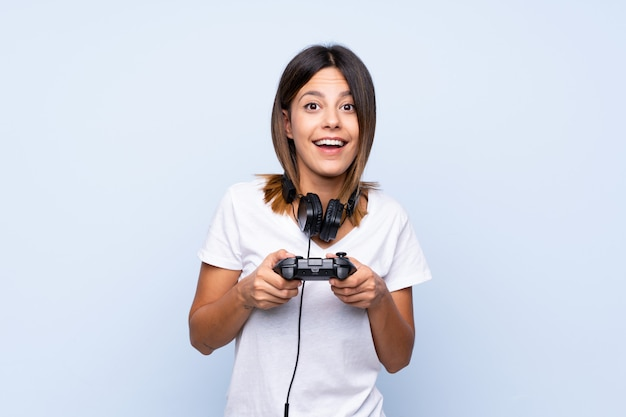 Giovane donna sopra il blu isolato giocando ai videogiochi