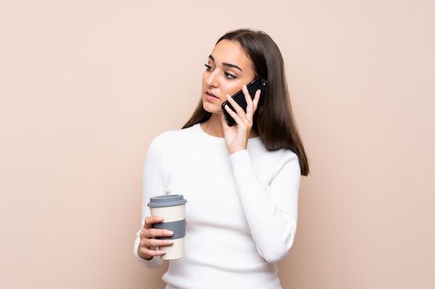 Giovane donna sopra il caffè isolato della tenuta da portare via e un cellulare