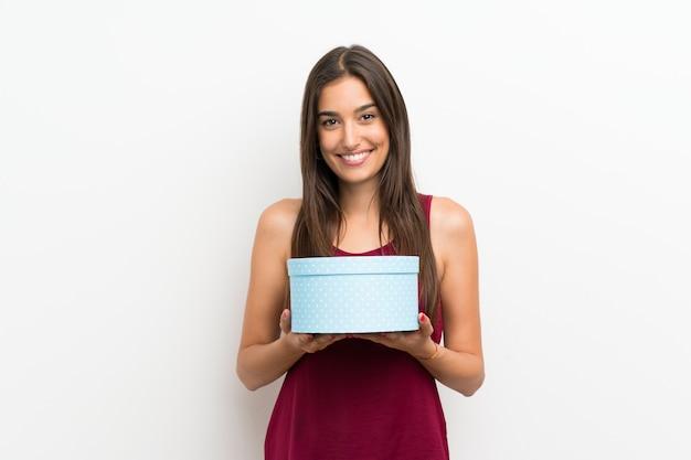 Giovane donna sopra il contenitore di regalo bianco isolato della tenuta della parete