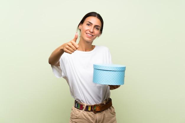 Giovane donna sopra il contenitore di regalo verde isolato della tenuta della parete