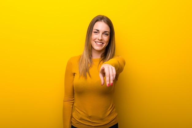 Giovane donna sopra il dito punti giallo con un'espressione fiduciosa