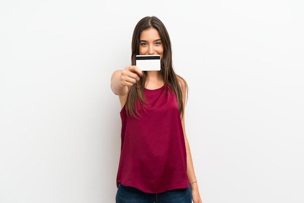 Giovane donna sopra il muro bianco isolato in possesso di una carta di credito