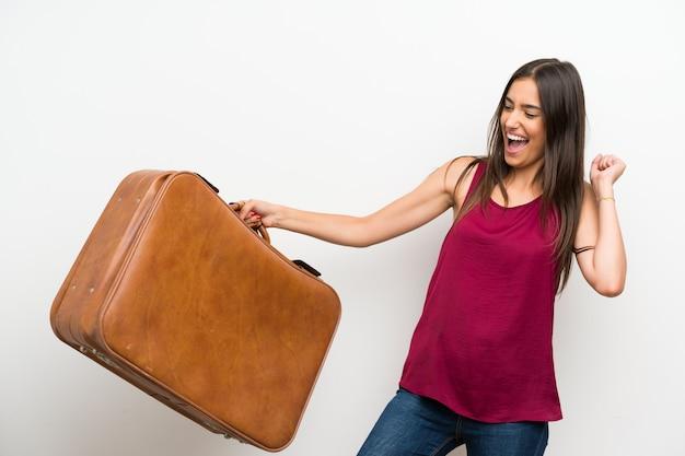Giovane donna sopra il muro bianco isolato in possesso di una valigetta vintage