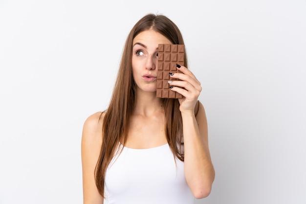 Giovane donna sopra il muro bianco isolato prendendo una tavoletta di cioccolato e sorpreso