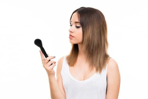 Giovane donna sopra isolato sfondo bianco con pennello trucco