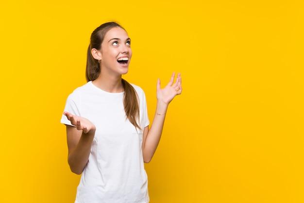 Giovane donna sopra isolato sfondo giallo con sorpresa espressione facciale