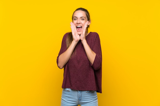 Giovane donna sopra isolato sfondo giallo, gridando e annunciando qualcosa