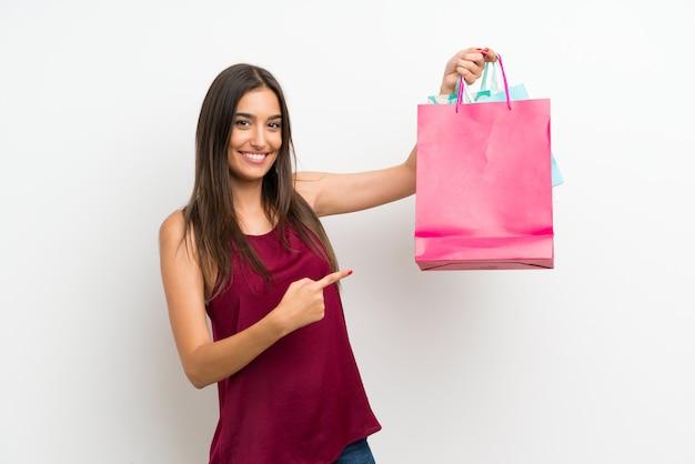 Giovane donna sopra la parete bianca isolata che tiene molti sacchetti della spesa