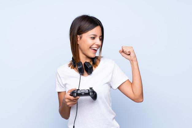 Giovane donna sopra la parete blu isolata che gioca ai videogiochi