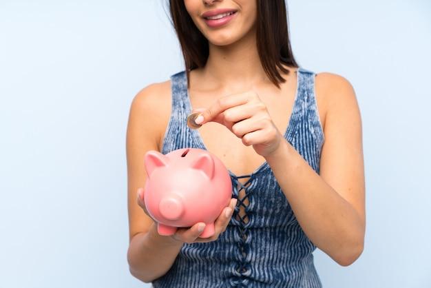 Giovane donna sopra la parete blu isolata che tiene un grande porcellino salvadanaio
