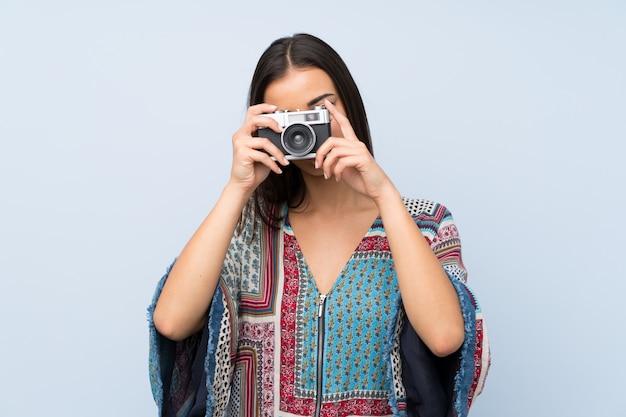 Giovane donna sopra la parete blu isolata che tiene una macchina fotografica
