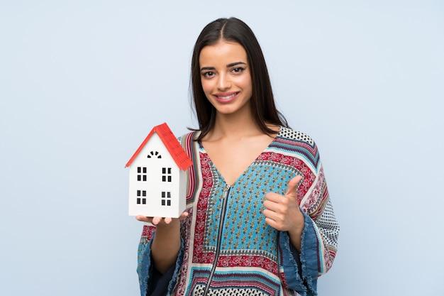 Giovane donna sopra la parete blu isolata che tiene una piccola casa