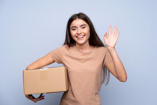 Giovane donna sopra la parete blu isolata che tiene una scatola per spostarla in un altro sito e salutare