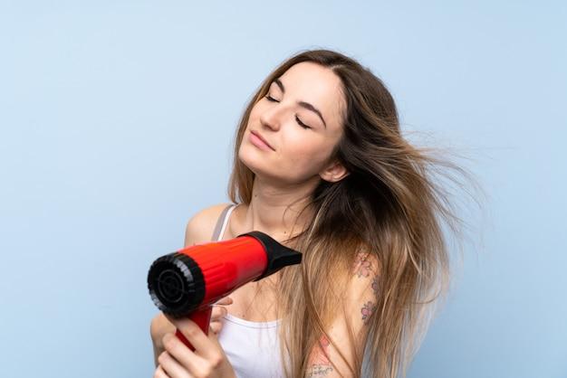 Giovane donna sopra la parete blu isolata con asciugacapelli