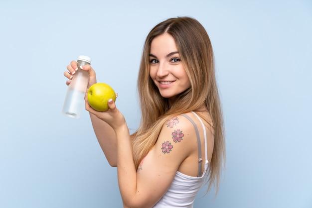 Giovane donna sopra la parete blu isolata con una mela e una bottiglia di acqua