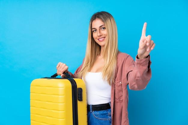 Giovane donna sopra la parete blu isolata in vacanza con la valigia di viaggio e contarne una