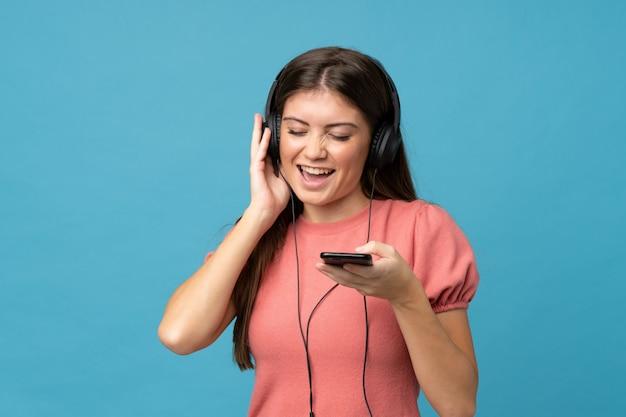 Giovane donna sopra la parete blu isolata usando il cellulare con le cuffie e cantando