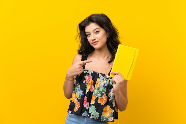 Giovane donna sopra la parete gialla isolata che tiene e che legge un libro