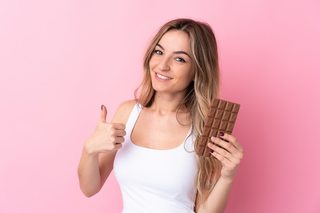 Giovane donna sopra la parete rosa isolata che prende una compressa del cioccolato e con il pollice su