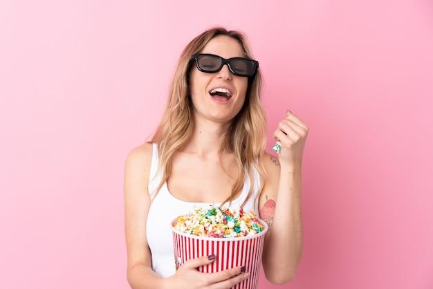 Giovane donna sopra la parete rosa isolata con gli occhiali 3d e in possesso di un grande secchio di popcorn