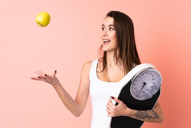 Giovane donna sopra la parete rosa isolata con la pesa e con una mela