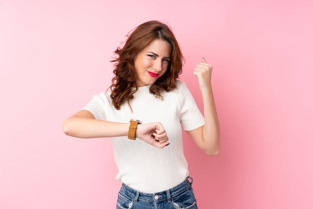 Giovane donna sopra la parete rosa isolata