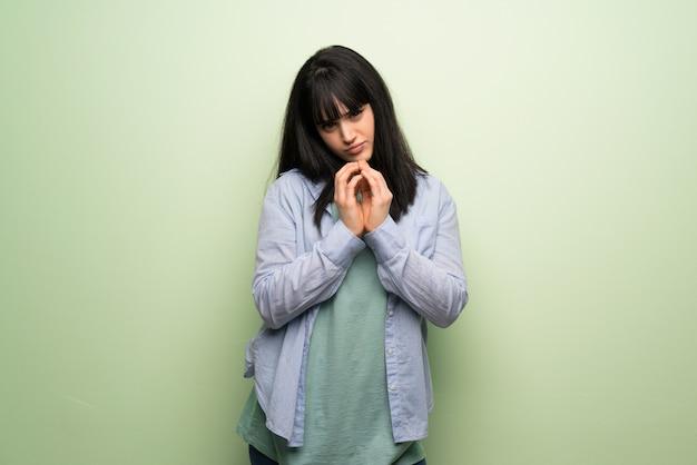 Giovane donna sopra la parete verde che intreccia qualcosa