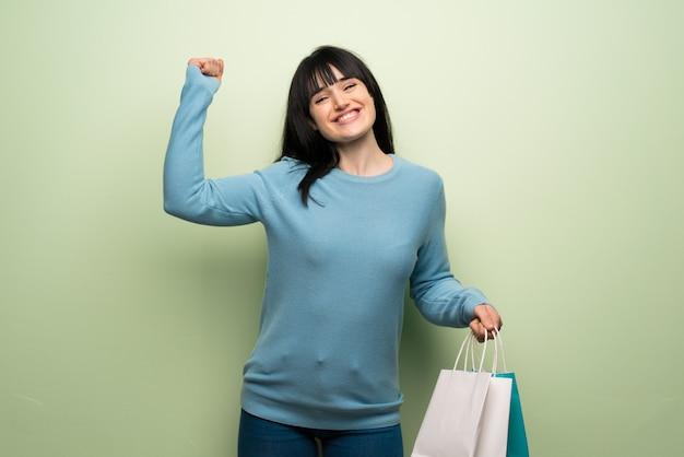 Giovane donna sopra la parete verde che tiene molti sacchetti della spesa nella posizione di vittoria
