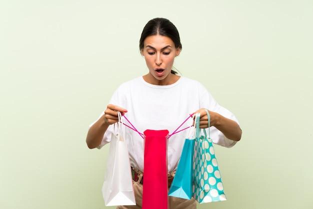 Giovane donna sopra la parete verde isolata che tiene molti sacchetti della spesa