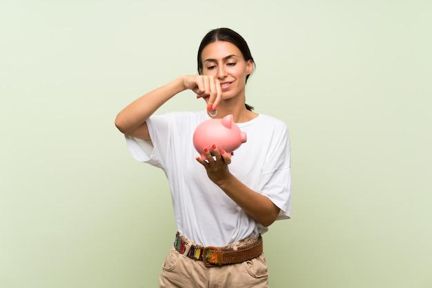 Giovane donna sopra la parete verde isolata che tiene un grande porcellino salvadanaio