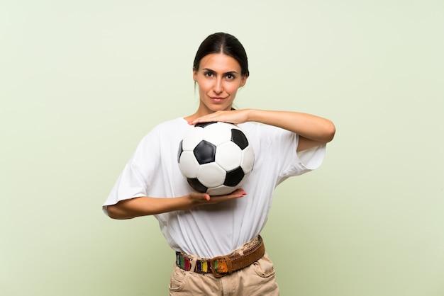 Giovane donna sopra la parete verde isolata che tiene un pallone da calcio