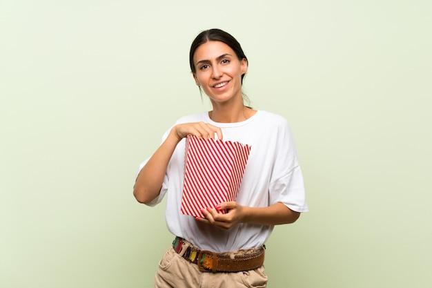 Giovane donna sopra la parete verde isolata che tiene una ciotola di popcorn