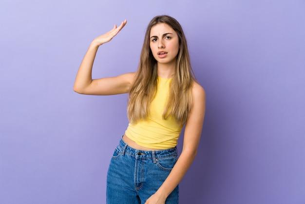 Giovane donna sopra la parete viola con espressione stanca e malata