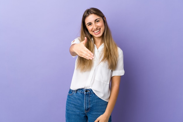 Giovane donna sopra la parete viola isolata che agita le mani per chiudere molto