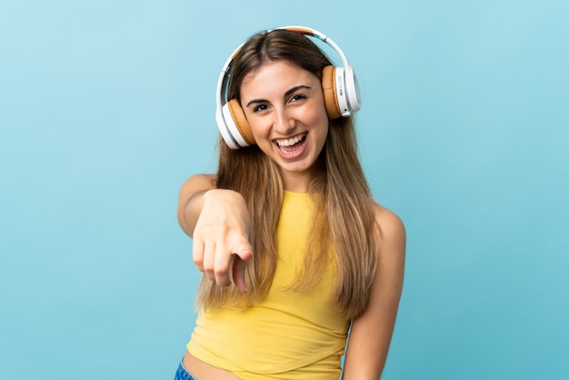 Giovane donna sopra musica d'ascolto isolata del fondo blu