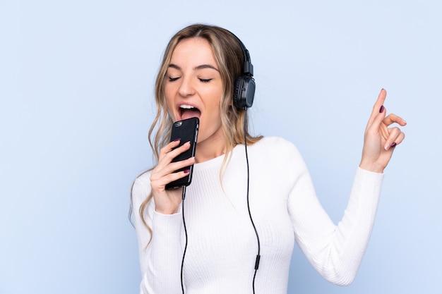 Giovane donna sopra musica d'ascolto isolata della parete blu con un cellulare e cantare