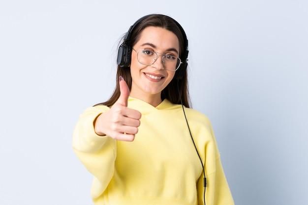 Giovane donna sopra musica d'ascolto isolata della parete blu e con il pollice in su