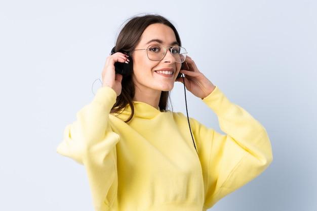 Giovane donna sopra musica d'ascolto isolata della parete blu
