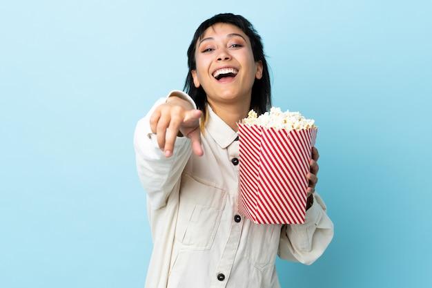 Giovane donna sopra spazio blu isolato che tiene un grande secchio di popcorn mentre punta davanti