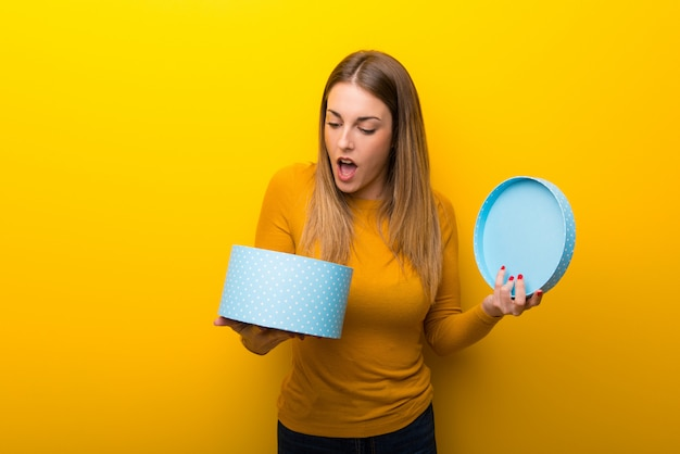 Giovane donna sopra sul contenitore di regalo giallo della tenuta in mani