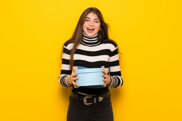 Giovane donna sopra sul muro giallo sorpreso perché gli è stato dato un regalo