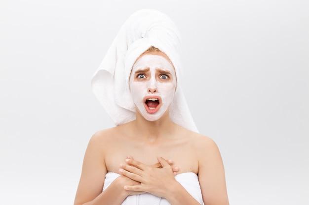 Giovane donna sorpresa con maschera cosmetica per il viso
